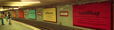 billboards opposite the waiting platform, including addresses + phone numbers